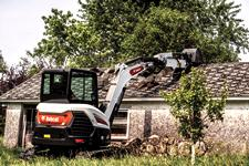Operator Using Bobcat E60 Compact Excavator With Extendable Arm And Clamp Attachment To Demolish House