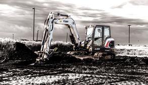 Bobcat E85 R-Series excavator and bucket attachment picks up and moves dirt.