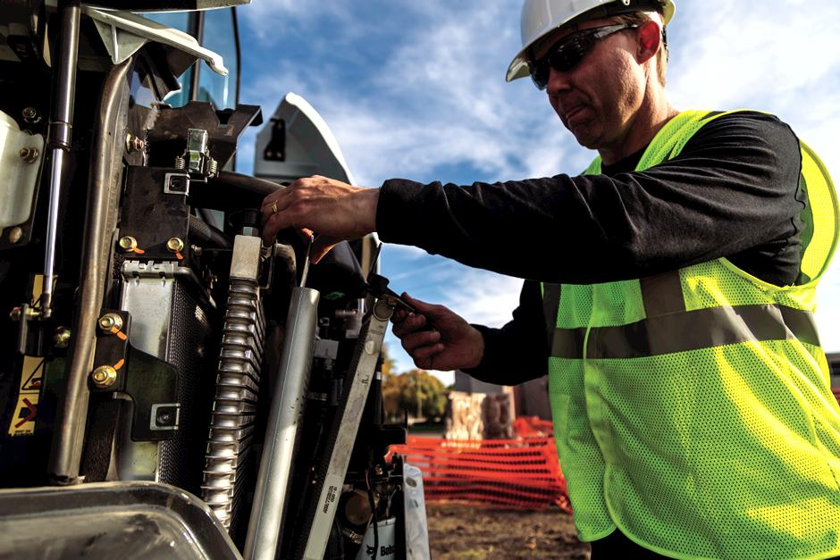 Construction Worker Performs Service Check On Bobcat E35 Mini Excavator