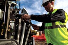 Operator works on a Bobcat (mini) excavator on maintenance with separable cooling cores.