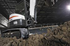 Bobcat E35 compact (mini) excavator backfills dirt in an arena.