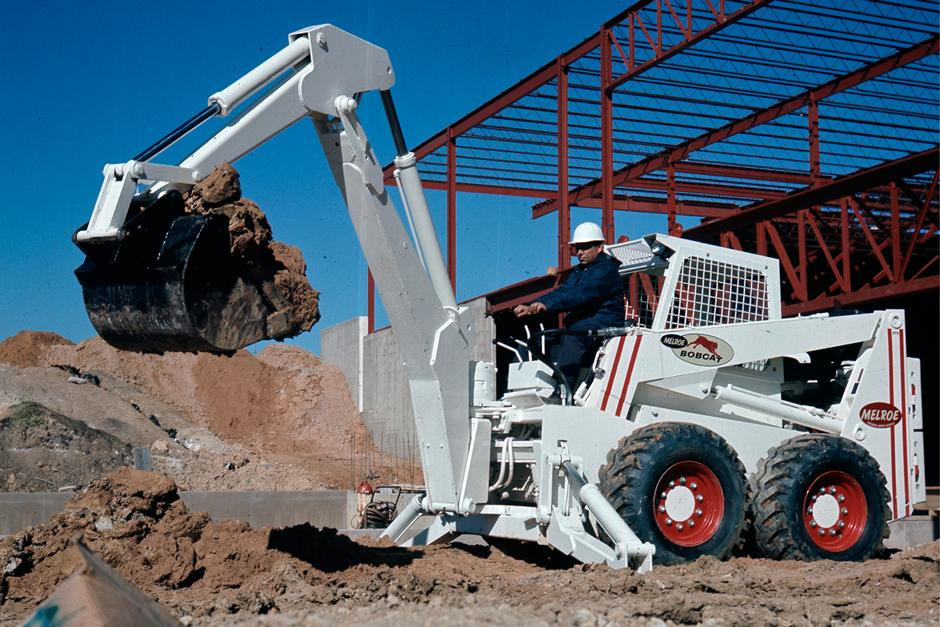 Melroe Bobcat Skid-Steer Loader With An Excavator Arm Attachment  Scooping Dirt