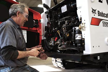 Service tech performs maintenance on compact equipment