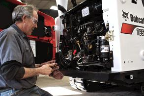 A service technician performs maintenance on compact equipment.