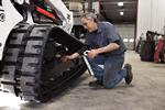 Service technician services a Bobcat compact track loader at a dealership.