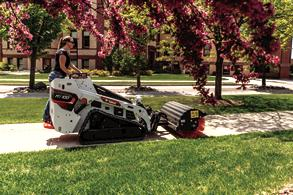 Grounds Maintenance Professional Sweeps Sidewalk With Angle Broom Attachment On Mini Skid Steer