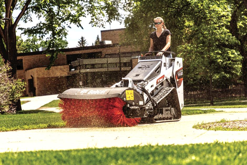 Groundskeeper Cleans Driveway With Mini Track Loader With Angle Broom Attachment