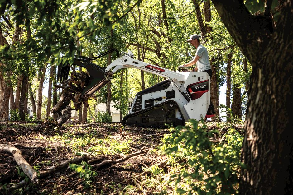 Homeowner Using Mini Skid Steer With Grapple Attachment In Woods