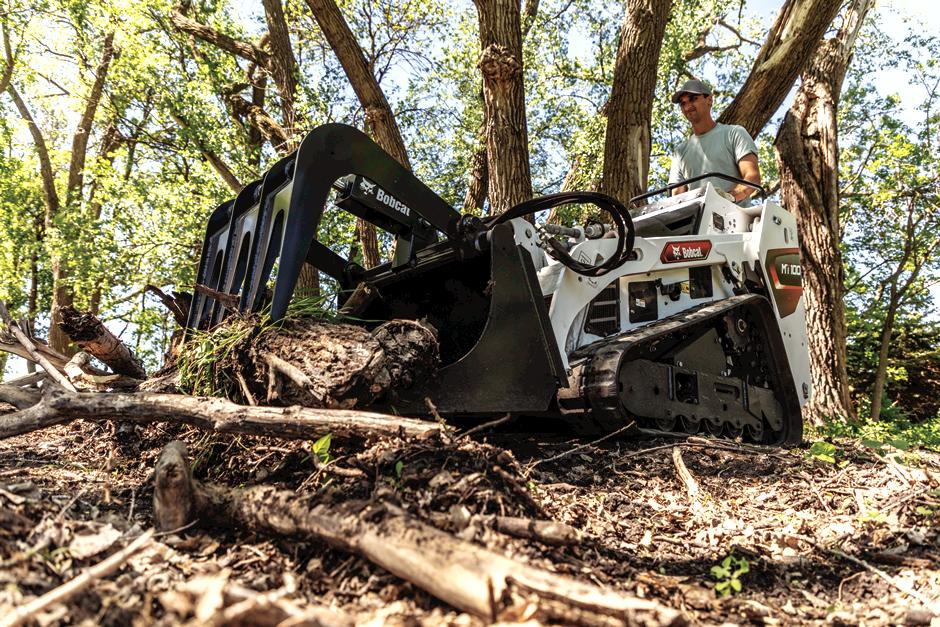 Low Angle Image Of Acreage Owner Using Mini Track Loader With Industrial Grapple Attachment To Move Large Tree Branches