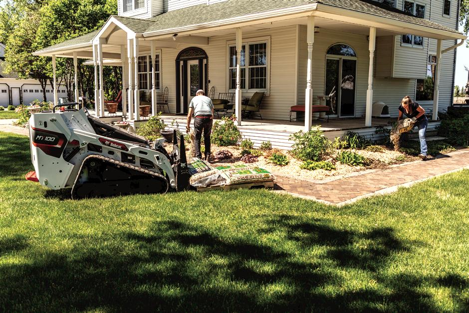 Landscaper Working On Landscape Around House With Mini Track Loader.