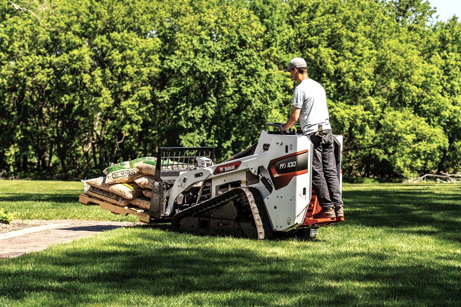 Landscaper Uses Mini Track Loader With Pallet Fork Attachment To Move Bags Of Mulch.