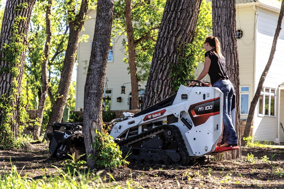 Homeowner Maneuvers Mini Track Loader Through Close Trees With Soil Conditioner Attachment.