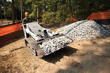 Bobcat Mini track loader with a general purpose bucket carries rock to create a foundation.