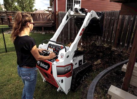 Landscaper Using Bobcat MT55 Mini Track Loader With Bucket Attachment To Dig In Lawn