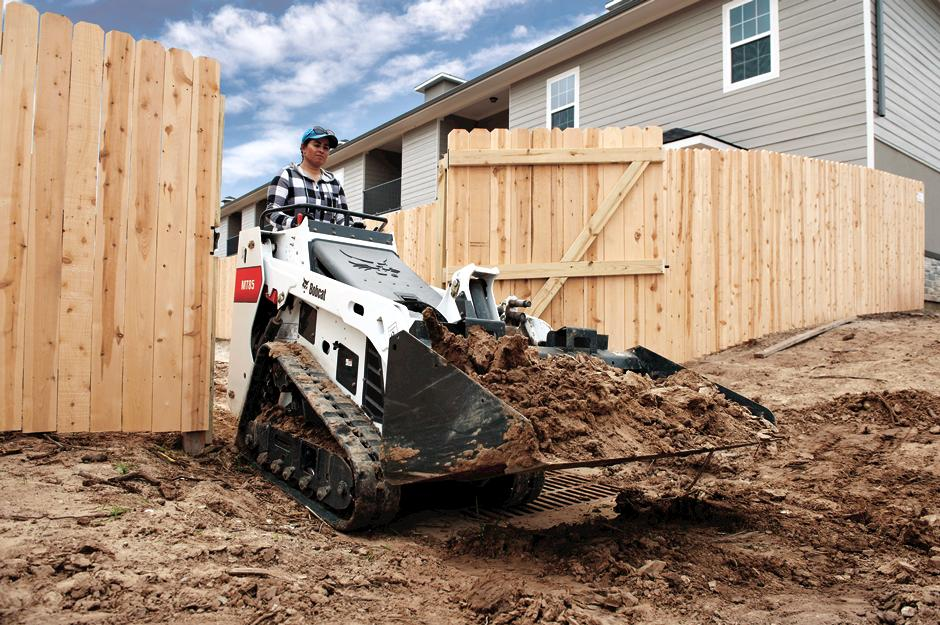 Landscaper Moving Dirt With Bobcat Mini Track Loader