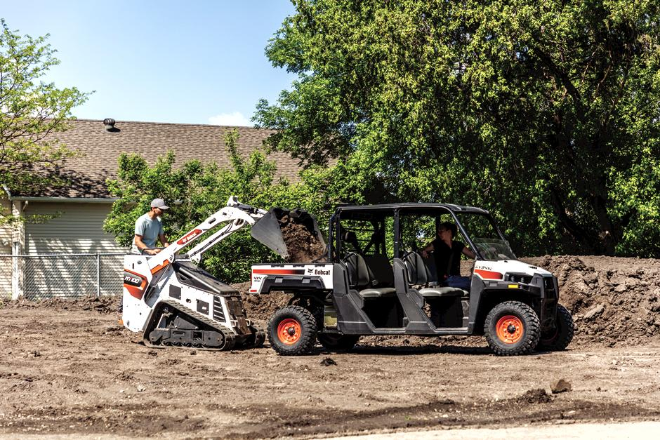 Landscaper Dumps Dirt From Mini Track Loader Into The Back Of A Utility Vehicle