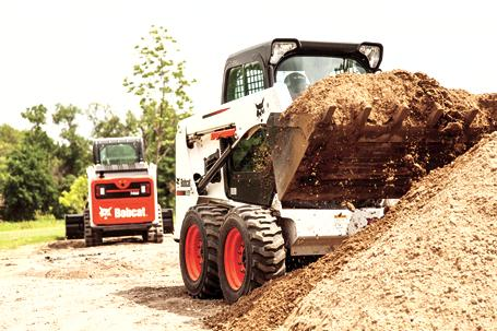 Bobcat S450 skid-steer loader and T450 compact-track loader transport dirt in buckets on a jobsite.