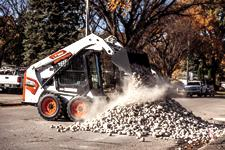 Bobcat S450 Skid-Steer Loader Dumping Landscape Rock Onto Pile