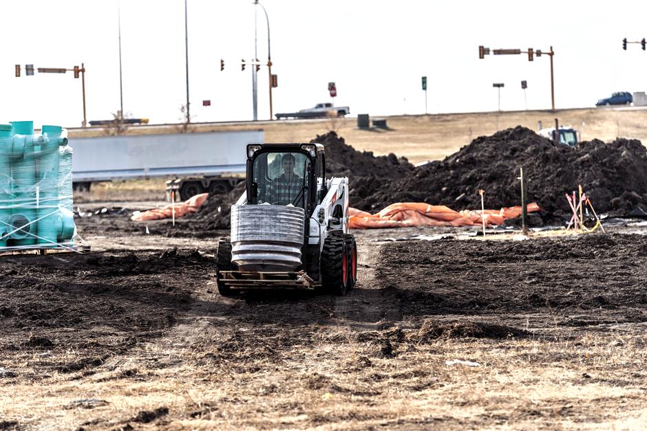 Bobcat S510 Skid-Steer Loader Carrying Heavy Materials Across Crowded Construction Area