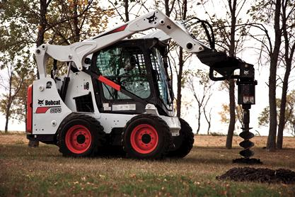 Bobcat S590 skid-steer loader uses planetary auger attachment to dig fence posts.