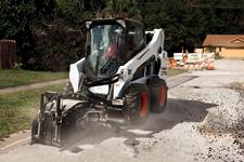 Bobcat S570 skid-steer loader with planer attachment works on a road construction project.