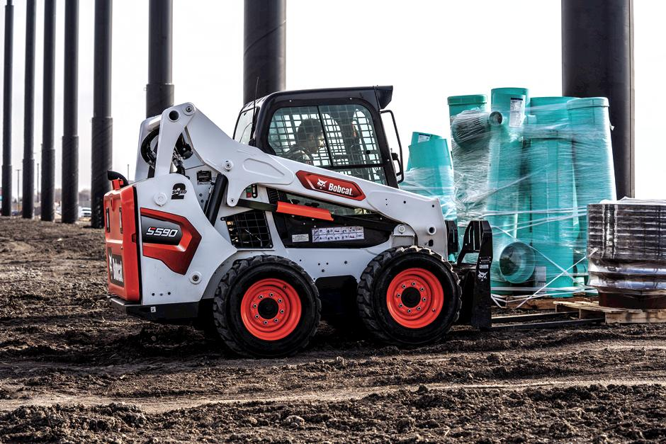 Operator Using Bobcat S590 Skid-Steer Loader With Pallet Fork Attachment To Move Materials On Jobsite