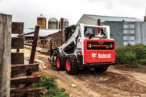 A Bobcat S595 skid-steer loader with root grapple attachment drives down lane heading toward farm buildings.