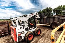 Bobca:Bobcat S595 skid-steer loader and bucket attachment filling a trailer with manure.