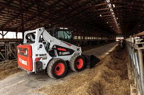 S595 skid-steer loader with a side lighting kit installed works in a dimly lit barn.