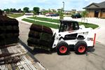 Bobcat S630 skid-steer loader removing rolls of sod from a trailer.