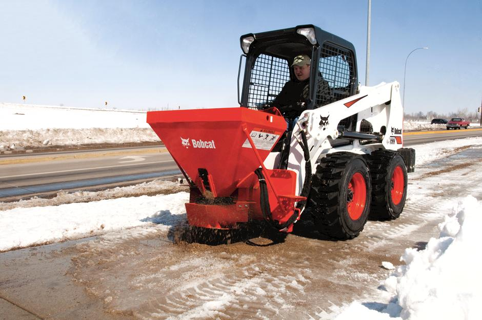 Operator Salts Icy Sidewalk With Spreader Attachment On Skid-Steer Loader