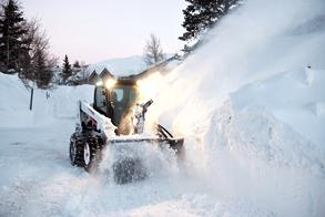 Bobcat Skid-Steer Loader Clears Snow Drift With Snow Blower Attachment