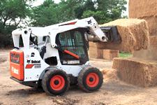 Bobcat S650 M2-Series skid-steer loader stacking bales of hay.