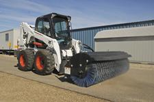 Bobcat S650 skid-steer loader and angle broom attachment sweep away debris on a path.