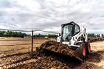 Bobcat S650 Skid-Steer Loader with bucket moving dirt on a farm.
