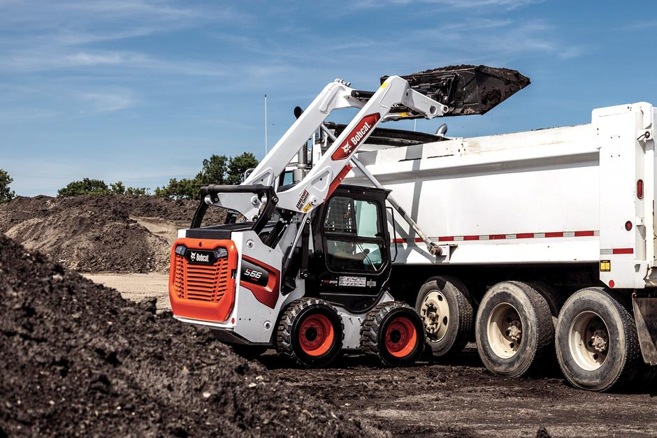 Bobcat T62 R-Series Compact Track Loader Lifts Material Off Of A Truck Bed On A Construction Site