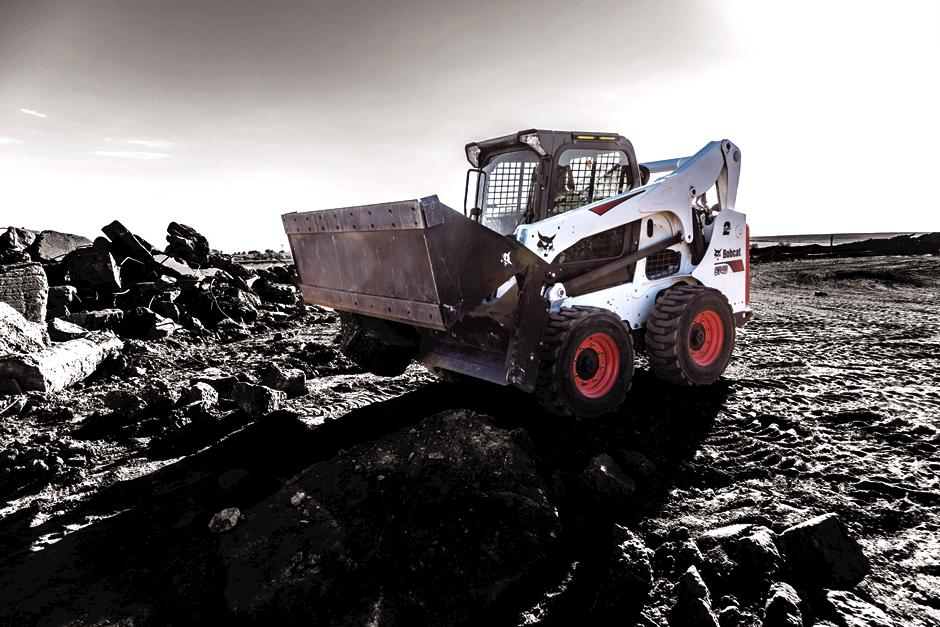 Bobcat S740 skid-steer loader and combination bucket moving rubble.