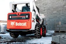 Bobcat S590Bobcat S740 skid-steer loader moving a pallet of cinder blocks.