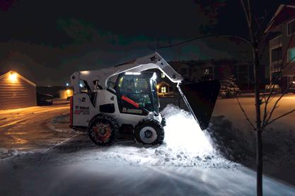 Bobcat snow bucket is used to pile up a snow in a parking lot.