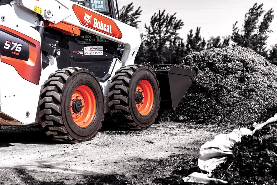 Operator Using Bobcat S76 Skid-Steer Loader With Bucket Attachment Moving Dirt.