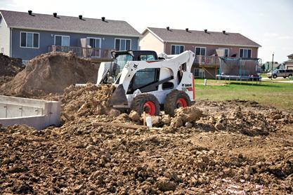Bobcat T630 compact track loader moves material with a dirt bucket.