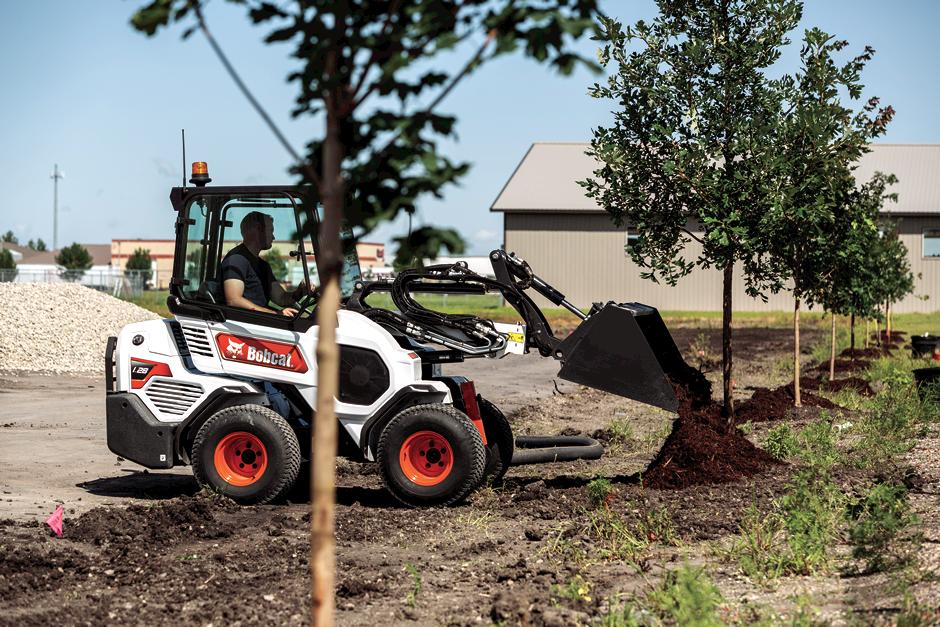 Landscaper Moving Rock With Bobcat Compact Track Loader