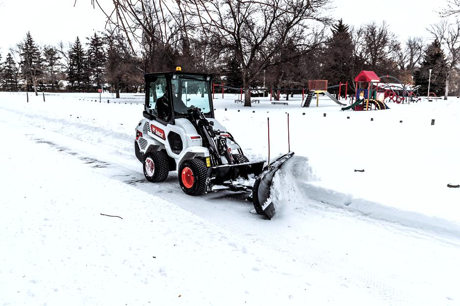 Operator Clears Sidewalk Of Snow Drifts With Snow Blade Attachment On Small Articulated Loader
