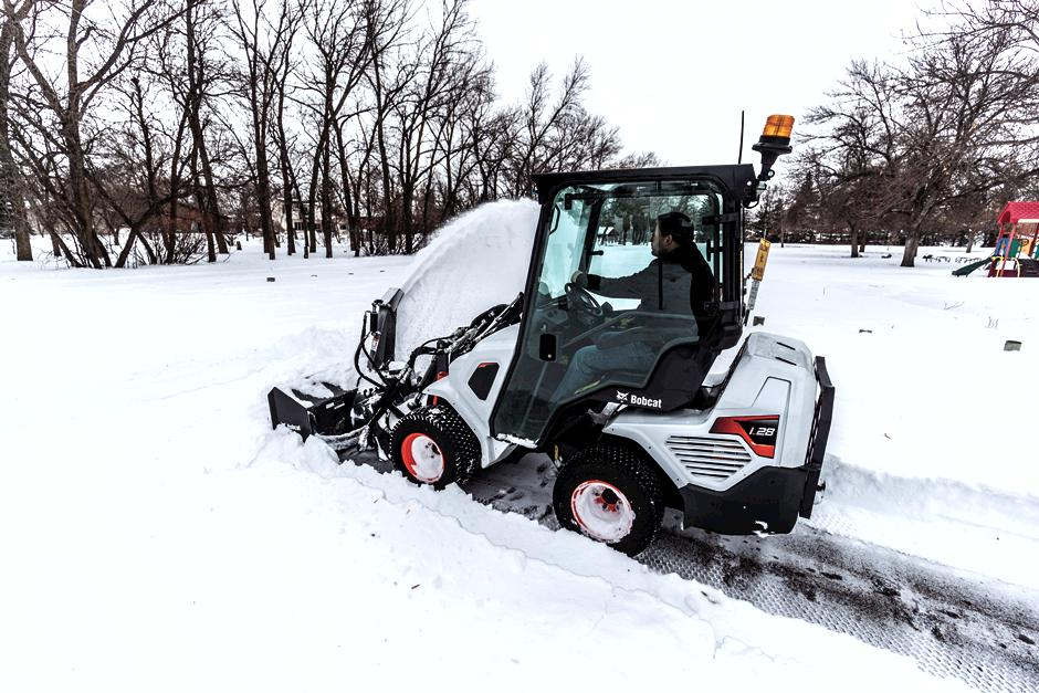 Operator Clears Sidewalk With Snowblower Attachment On Small Articulated Loader
