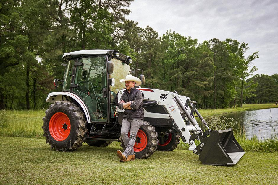 Country Singer Justin Moore Standing Next To His Bobcat Compact Tractor.