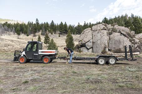 An operator attaches a flatbed trailer to a Toolcat 5600.