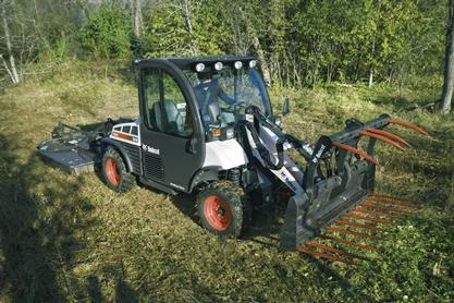 Toolcat 5610 mows grass in a wooded area.