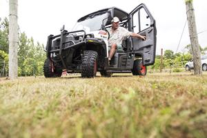 Operator closes the door of a Bobcat 3400 utility vehicle.