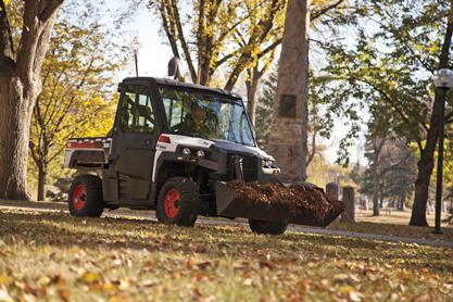 3650 UTV with Bobcat bucket attachment carries mulch while on a wooded path.