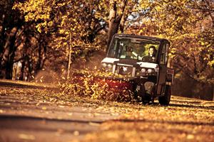 An angle broom attachment on the Bobcat 3650 utility vehicle is used to sweep leaves on a paved path.